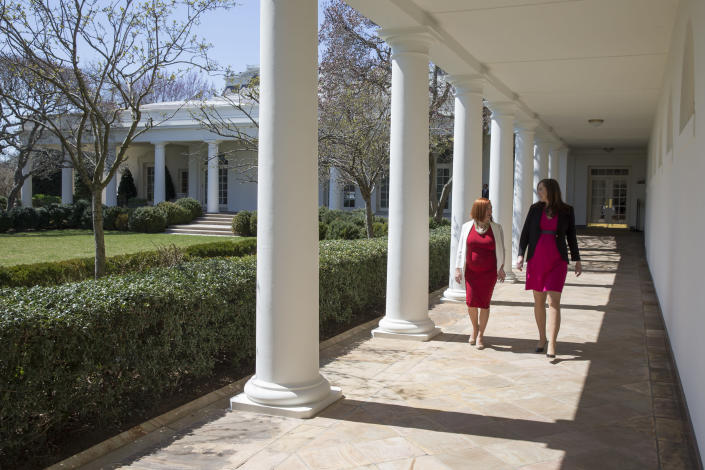 FILE - In this April 1, 2015, file photo Jen Psaki, left, and Katie Fallon walk through the West Colonnade of the White House in Washington. (AP Photo/Evan Vucci, File)