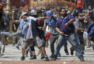 <p>Demonstrators throw objects at police during a general strike against a pension reform measure in Buenos Aires, Argentina, Monday, Dec. 18, 2017. Union leaders complain the legislation, which already passed in the Senate, would cut pension and retirement payments as well as aid for some of poor families. (AP Photo/Natacha Pisarenko) </p>