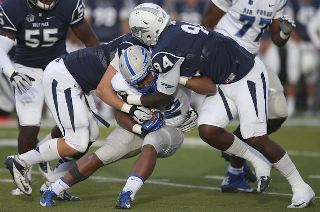 Air Force's Broam Hart (32) gets tackled by Nevada's Jordan Dobrich, left, and Lenny Jones (94) during the first half of an NCAA college football game in Reno, Nev., on Saturday, Sept. 28, 2013. (AP Photo/Cathleen Allison)