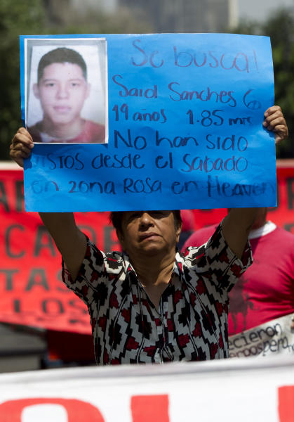"""A woman holds up a sign with details of her recently disappeared relative during a protest in Mexico City, Thursday, May 30, 2013. Eleven young people were kidnapped in broad daylight from a Mexico City bar, just 20 days after the grandson of civil rights leader Malcolm X was beaten to death at a nightclub in the capital, anguished relatives said Thursday. The sign reads in Spanish """"Looking for Said Sanches, 19-years-old, 1.85 meters, has not been seen since Saturday in Zona Rosa in Heaven."""" The mother of one of the missing youths says 11 people in all vanished from the after-hours club about 1 ½ blocks from the U.S. embassy, on the other side of Reforma Avenue. (AP Photo/Eduardo Verdugo)"""