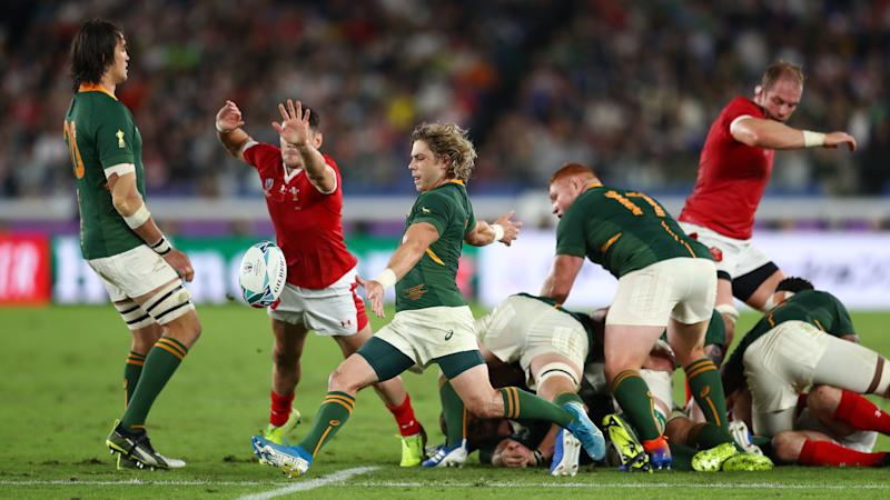 YOKOHAMA, JAPAN - OCTOBER 27: Faf de Klerk of South Africa kicks away from the scrum as Tomos Williams of Wales challenges during the Rugby World Cup 2019 Semi-Final match between Wales and South Africa at International Stadium Yokohama on October 27, 2019 in Yokohama, Kanagawa, Japan. (Photo by Michael Steele/2019 Getty Images)