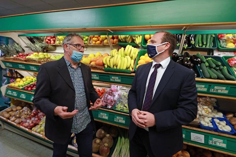 Economy Minister Gordon Lyons (right) speaks to Michael Goggin, owner of Michel's fruit and vegetable shop on the Ormeau Road in Belfast (Liam McBurney/PA) (PA Wire)