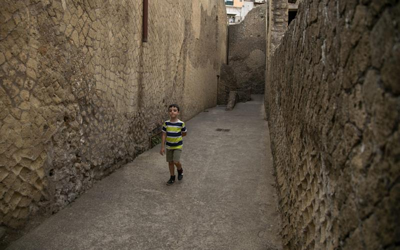 A child visits the ancient Roman city of Herculaneum, destroyed in 79AD by the eruption of Vesuvius, on the day of the reopening of the archaeological park in Ercolano, Italy - Ivan Romano/Getty Images
