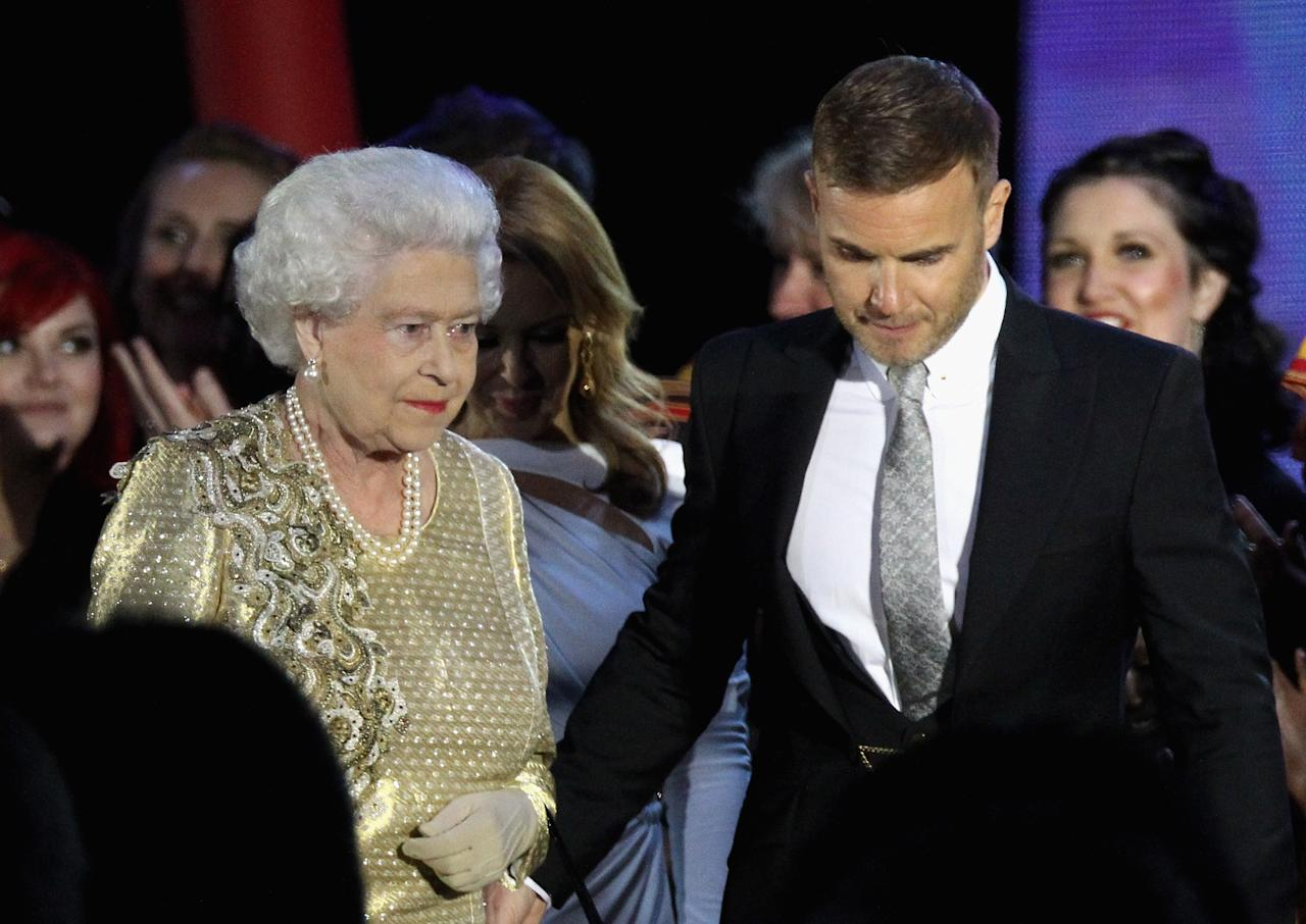LONDON, ENGLAND - JUNE 04:  HM Queen Elizabeth II and musician Gary Barlow on stage during the Diamond Jubilee concert at Buckingham Palace on June 4, 2012 in London, England. For only the second time in its history the UK celebrates the Diamond Jubilee of a monarch. Her Majesty Queen Elizabeth II celebrates the 60th anniversary of her ascension to the throne. Thousands of well-wishers from around the world have flocked to London to witness the spectacle of the weekend's celebrations.  (Photo by Dan Kitwood/Getty Images)