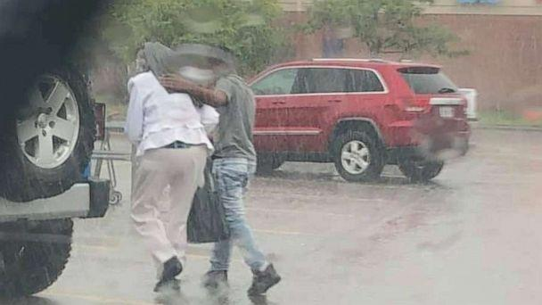 PHOTO: An officer snapped a photo of a young man getting out of his car to help shield a woman from the rain. (Independence Police Department)