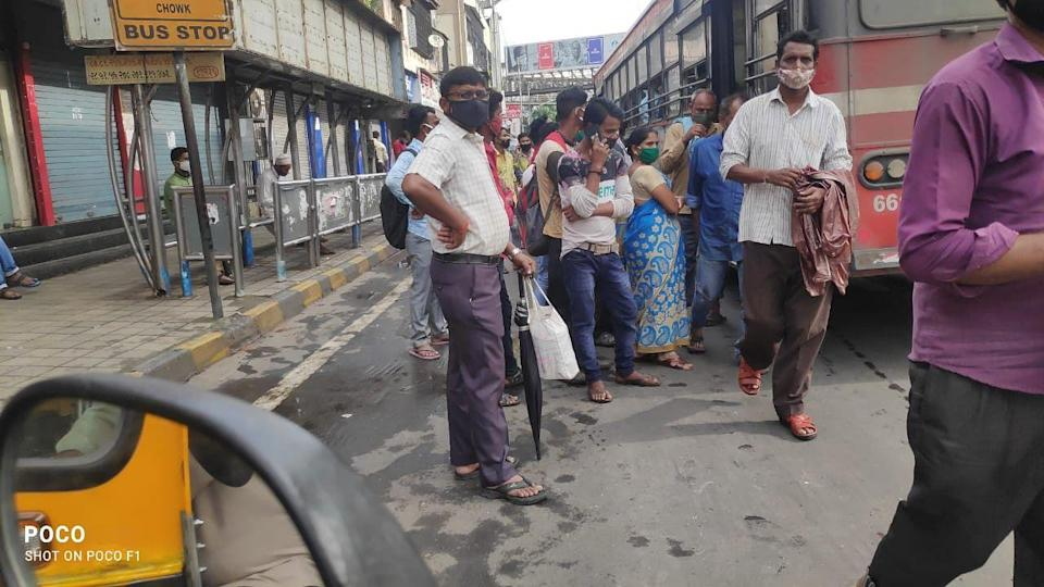 Crowd at a bus stop.
