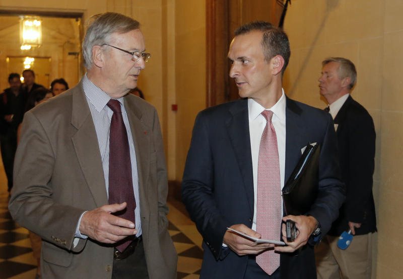 The head of the U.S. Anti-Doping Agency, Travis Tygart, right, speaks with former French anti-doping agency (AFLD) president Pierre Bordry, left, before a senate-led inquiry into the fight against doping in Paris, France, Thursday, April 25, 2013. USADA produced a scathing report detailing systematic doping by Lance Armstrong and his teams, which led to Armstrong being stripped of his seven Tour titles and banned from elite sport for life. (AP Photo/Francois Mori)