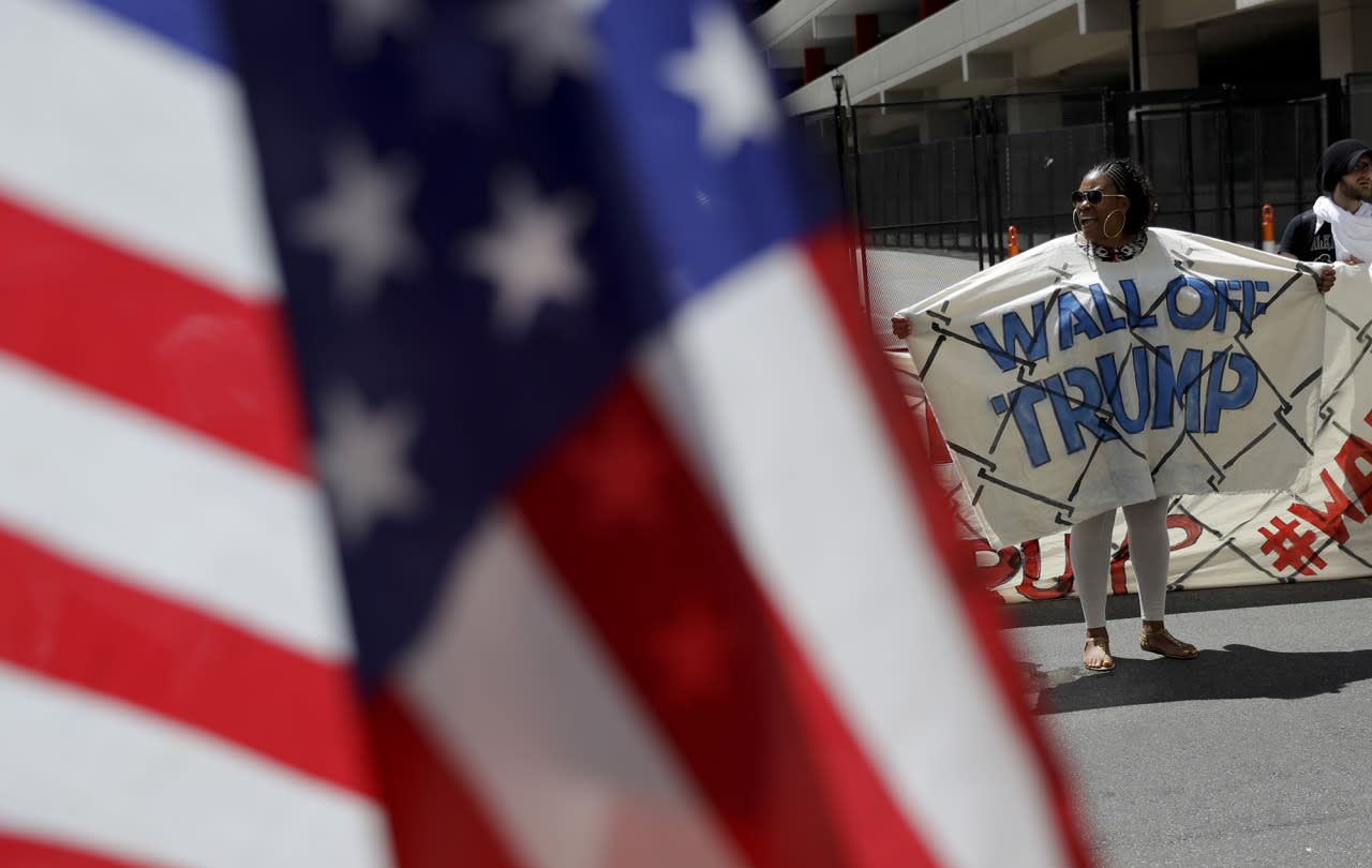<p>A immigrant rights activist holds up part of a fabric wall protesting Republican presidential candidate Donald Trump, July 20, 2016, in Cleveland, during the third day of the Republican convention. (Photo: Patrick Semansky/AP)</p>