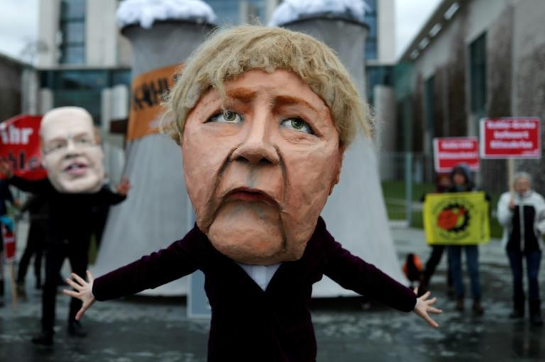 """Outside Chancellor Angela Merkel's office, marchers brandished signs reading """"Shut off the coal plants NOW"""""""