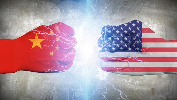 Two fists facing each other, one painted with China flag and one with U.S. flag.