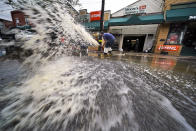 Water is pumped from the basement of a business on Noblestown road in Oakdale, Pa., during clean up from flooding after downpours and high winds from the remnants of Hurricane Ida, hit the area Wednesday, Sept. 1, 2021. (AP Photo/Gene J. Puskar)