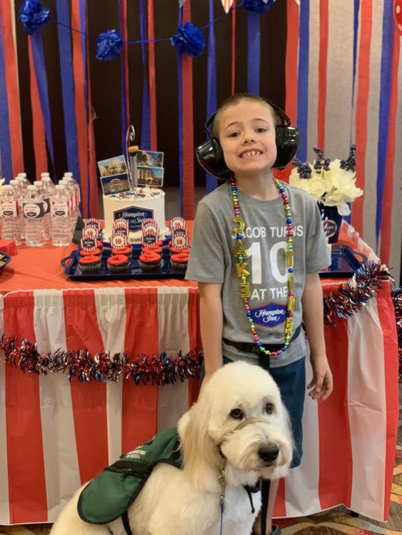 A boy with autism is smiling at his birthday party standing by a table with a cake and cupcakes.