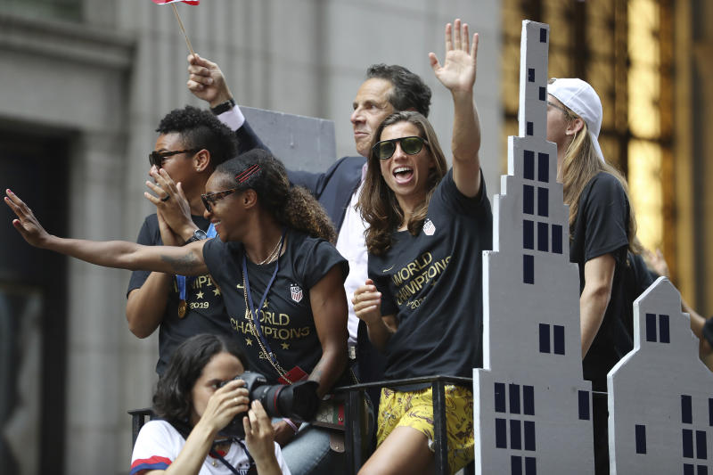 United States defender Crystal Dunn, center, and United States forward Tobin Heath, right, wave to the crowd on a float while being honored with a ticker tape parade along the Canyon of Heroes, Wednesday, July 10, 2019, in New York. The U.S. national team beat the Netherlands 2-0 to capture a record fourth Women's World Cup title. (AP Photo/Steve Luciano)