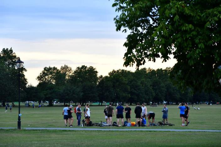 Friends enjoy a drink on Clapham Common in London