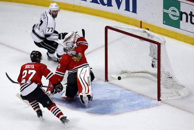 Los Angeles Kings center Jeff Carter (77) scores a goal against Chicago Blackhawks goalie Corey Crawford (50) as the Blackhawks defenseman Johnny Oduya (27) watches during the first period in Game 7 of the Western Conference finals in the NHL hockey Stanley Cup playoffs Sunday, June 1, 2014, in Chicago. (AP Photo/Charles Rex Arbogast)
