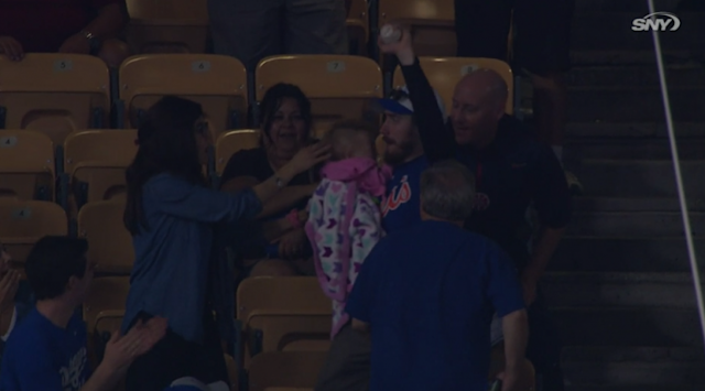 This Mets fan caught the ball while holding his baby, but mom didn't seem very amused. (MLB.TV)