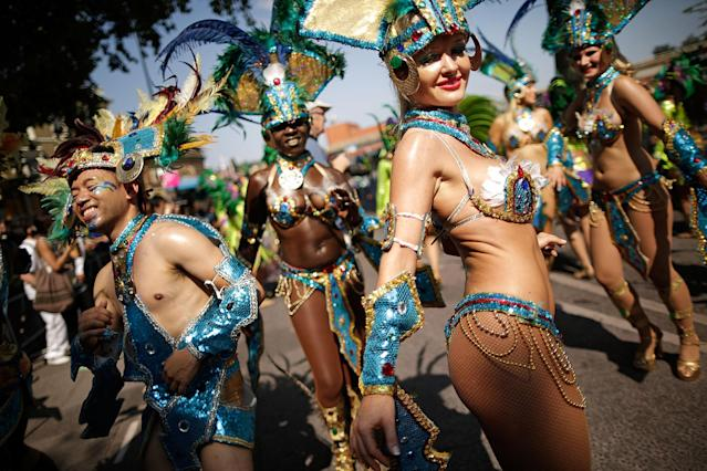 LONDON, ENGLAND - AUGUST 26: Performers parade past the judges position at the start of the Notting Hill Carnival on August 26, 2013 in London, England. More than one million people are expected to enjoy this year's Notting Hill Carnival. It is the largest street festival in Europe and was first held in 1964 by the Afro-Caribbean community. Over the bank holiday weekend the streets come alive to steel bands, colourful floats and costumed performers as members of the public flood into the area to join in the celebrations. (Photo by Matthew Lloyd/Getty Images)