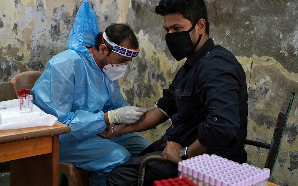 A healthcare worker wearing a protective gear collects blood sample from a man, who has recovered from the coronavirus disease, during a plasma donation camp inside a classroom at a slum in Mumbai, India - HEMANSHI KAMANI/ REUTERS