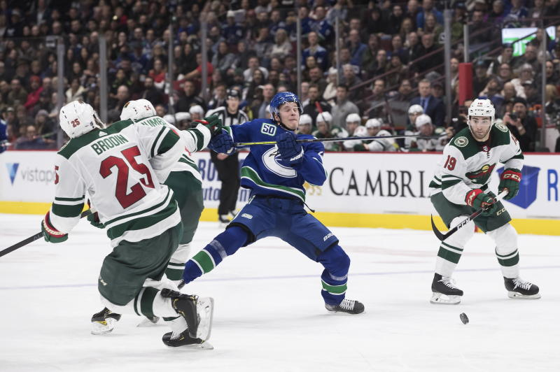 Vancouver Canucks' Elias Pettersson, center, of Sweden, is checked by Minnesota Wild's Matt Dumba (24) during the second period of an NHL hockey game Wednesday, Feb. 19, 2020, in Vancouver, British Columbia. (Darryl Dyck/The Canadian Press via AP)