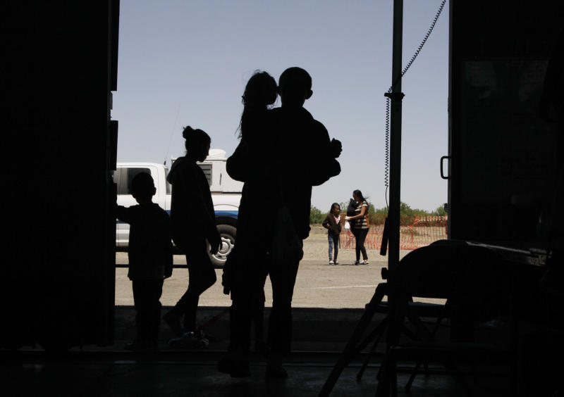 FILE - In this Wednesday, May 22, 2019 file photo migrants mainly from Central America guide their children through the entrance of a World War II-era bomber hanger in Deming, N.M. A panel of appeals court judges in California will hear arguments in the long-running battle between advocates for immigrant children and the U.S. government over conditions in detention and holding facilities near the southwest border. (AP Photo/Cedar Attanasio, File)