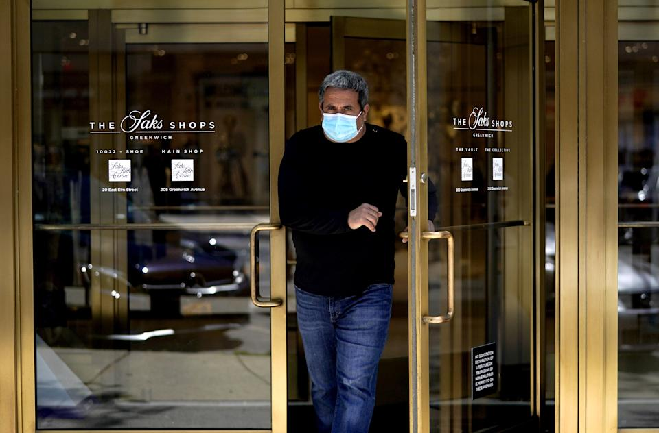 A man comes out of Saks Fifth Avenue on Greenwich Avenue in Greenwich, Connecticut on May 20, 2020 as Phase 1 of Reopening Connecticut begins today. - All 50 US states have now partially emerged from coronavirus lockdowns. Connecticut became the final state to begin lifting restrictions. (Photo by TIMOTHY A. CLARY / AFP) (Photo by TIMOTHY A. CLARY/AFP via Getty Images)