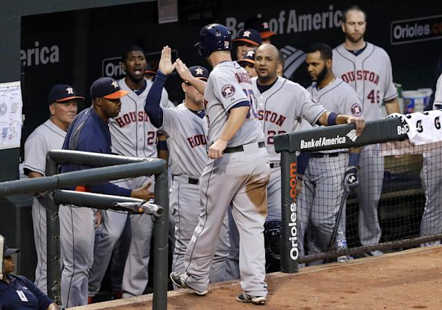Houston Astros' Matt Dominguez, center, greets teammates in the dugout after scoring on a fly out by L.J. Hoes in the third inning of baseball game against the Baltimore Orioles, Friday, May 9, 2014, in Baltimore. (AP Photo/Patrick Semansky)