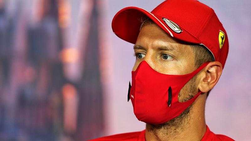 Ferrari F1 driver Sebastian Vettel is pictured wearing a mask during a press conference.