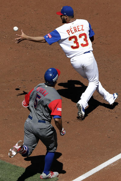 Venezuela pitcher Martin Perez (33) bobbles a toss from teammate infielder Hernan Perez as Puerto Rico's T.J. Rivera (5) reaches first base during the third inning of a second-round World Baseball Classic baseball game Saturday, March 18, 2017, in San Diego. (AP Photo/Gregory Bull)