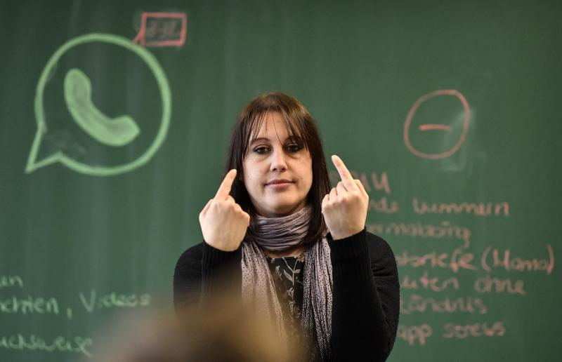 Teacher Vera Servaty reacts to pupils during a lesson in social media and internet at a comprehensive school in Essen, Germany, Monday, March 18, 2019. Experts and teachers say that peer projects in which teenagers teach younger school mates how to deal with digital stress like constant messaging or cyber-bullying have proven to be especially successful. (AP Photo/Martin Meissner)
