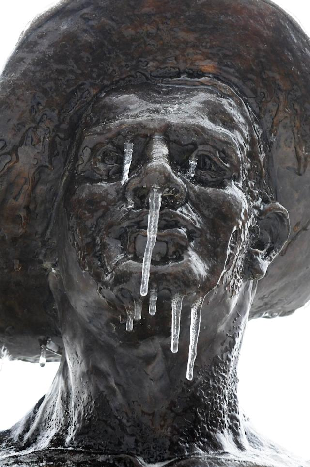 """Icicles hang from the statue of """"The Worker"""" at Henderson's Audubon State Park Wednesday morning, Feb. 5, 2014, after a over night ice storm moved through the area. (AP Photo/The Gleaner, Mike Lawrence)"""