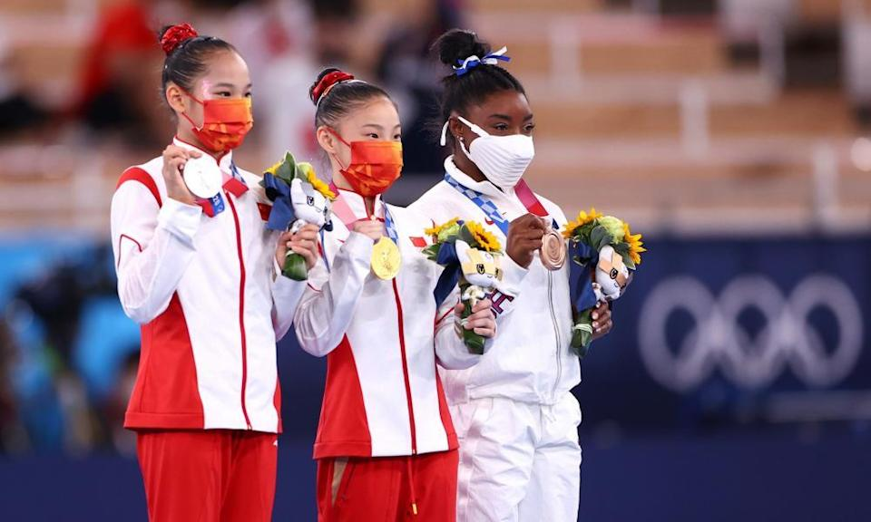 Gold medallist Guan Chenchen of China celebrates on the podium with silver medallist, Tang Xijing of China and bronze medallist, Simone Biles of the US.