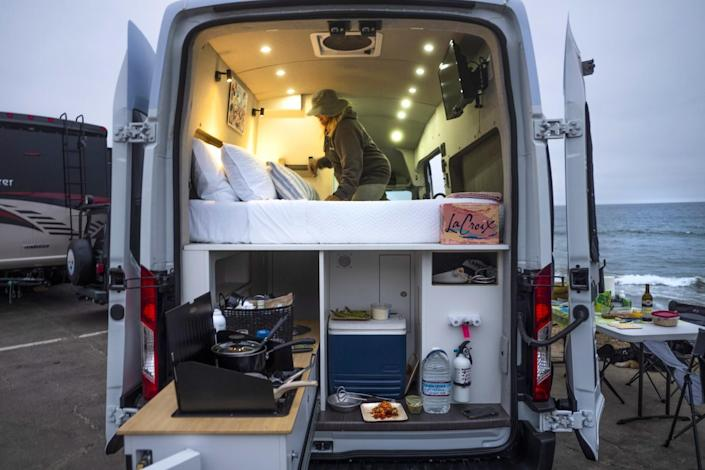 The back of a van shows a bed and compartments for cooking and food storage
