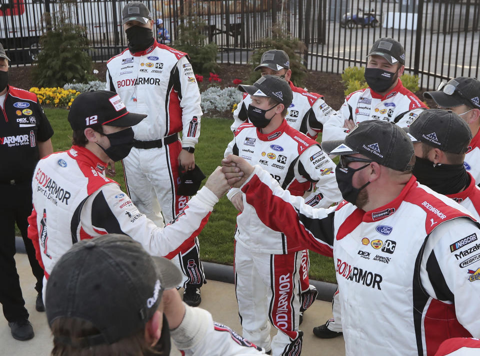 Ryan Blaney, left, gives his pit crew fist-bumps after a NASCAR Cup Series auto race at Atlanta Motor Speedway on Sunday, March 21, 2021, in Hampton, Ga. (Curtis.Compton/Atlanta Journal-Constitution via AP)