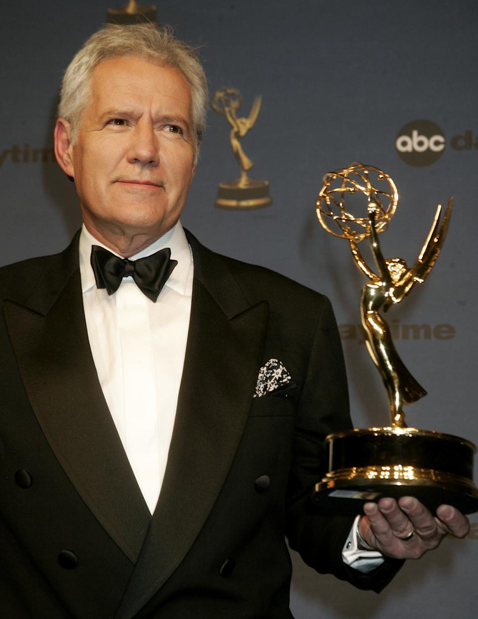 """Alex Trebek, host of the game show """"Jeopardy"""" poses with his Emmy award at the 33rd annual Daytime Emmy Awards in Hollywood, California April 28, 2006. Trebek won as outstanding game show host. REUTERS/Fred Prouser"""