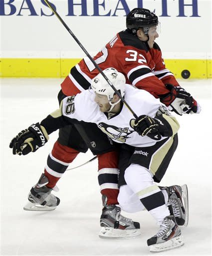 Pittsburgh Penguins' Joe Vitale (46) and New Jersey Devils' Matt Taormina (32) compete for the puck during the third period of an NHL hockey game on Sunday, Feb. 5, 2012, in Newark, N.J. The Devils won 5-2. (AP Photo/Julio Cortez)