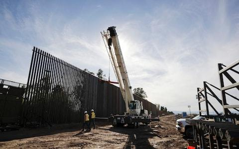 Construction continues on a new, taller version of the border structure in Calexico, Calif - Credit: AP