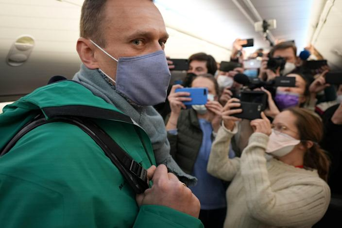 Alexei Navalny is surrounded by journalists inside the plane prior to his flight to Moscow in the Airport Berlin Brandenburg in Schoenefeld, near Berlin, Germany,  Jan. 17, 2021.