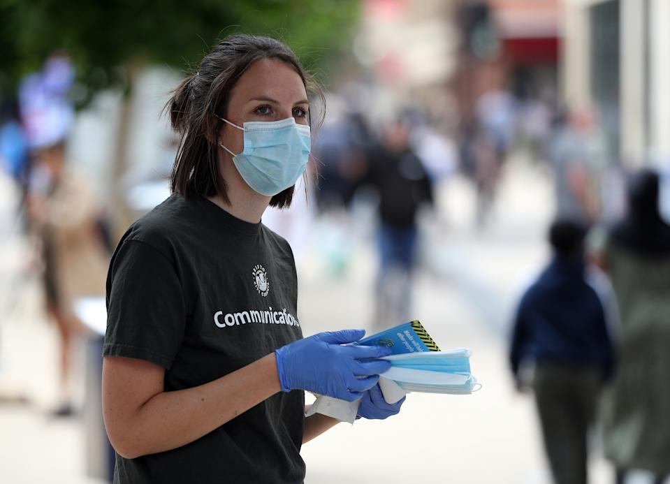 Bristol City Council staff hand out 80,000 face masks in Bristol city centre as face coverings become mandatory in shops and supermarkets in England. (Photo by Andrew Matthews/PA Images via Getty Images)