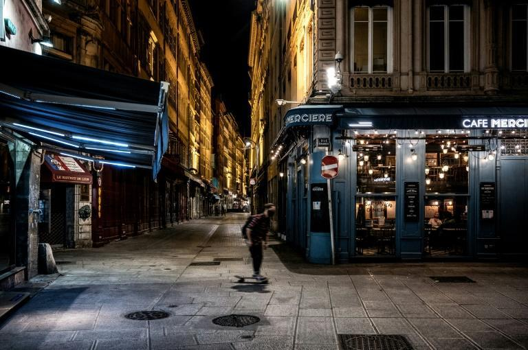 A man rides his skateboard past the deserted Lyon rue Merciere during the first night of curfew