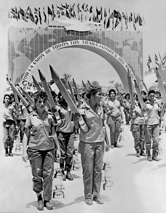 Young women working for a literacy campaign take part in a parade with big pencils in the streets of Havana in May 1961 during the Cuban Revolution.