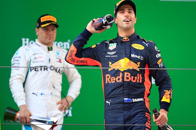 Formula One F1 - Chinese Grand Prix - Shanghai International Circuit, Shanghai, China - April 15, 2018 Red Bull's Daniel Ricciardo celebrates with a shoe after winning the race as Mercedes' Valtteri Bottas looks on REUTERS/Aly Song