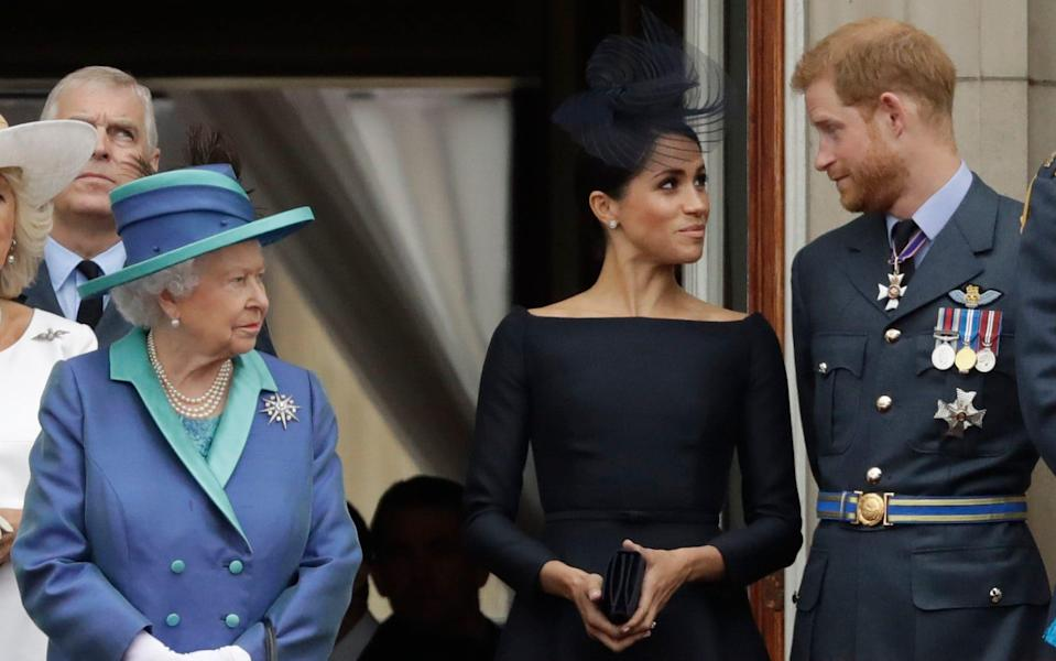 The Queen and the Duke and Duchess of Sussex pictured together on the balcony of Buckingham Palace in London in July 2018 - Matt Dunham/AP