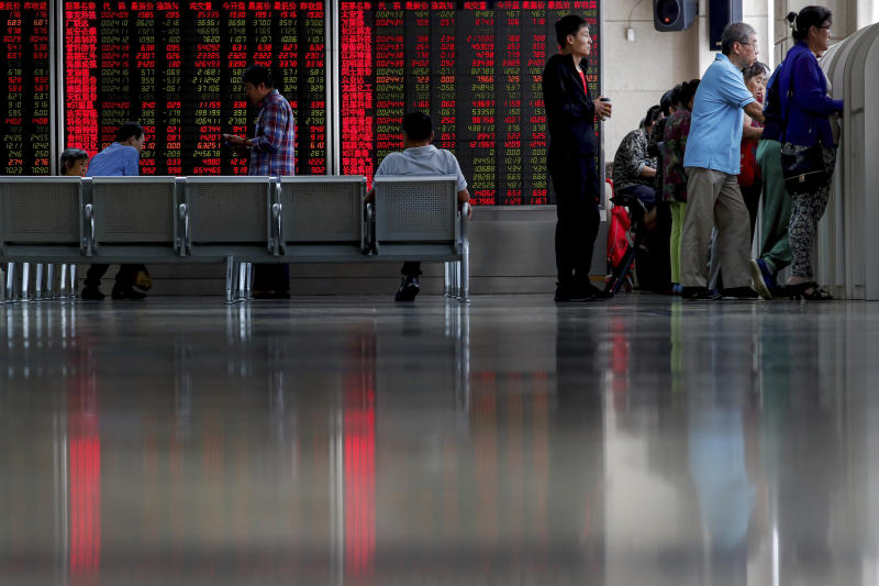 Chinese investors check stock prices at a brokerage house in Beijing, Thursday, Sept. 19, 2019. Shares were mixed in Asia on Thursday, with Tokyo and Sydney logging modest gains after the Federal Reserve cut its benchmark interest rate for a second time this year, citing slowing global economic growth and uncertainty over U.S. trade conflicts. (AP Photo/Andy Wong)