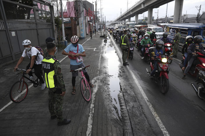 Police inspect motorists at a checkpoint during a stricter lockdown as a precaution against the spread of the coronavirus on the outskirts of Marikina City, Philippines on Friday, August 6, 2021. Thousands of people jammed coronavirus vaccination centers in the Philippine capital, defying social distancing restrictions, after false news spread that unvaccinated residents would be deprived of cash aid or barred from leaving home during a two-week lockdown that started Friday. (AP Photo/Basilio Sepe)