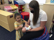 This May 4, 2021 image shows child development director Paola Castillo playing with Arelyanna, 3, one of the students at Cuidando Los Ninos in Albuquerque, N.M. The charity provides housing, child care and financial counseling for mothers, all of whom will benefit from expanded Child Tax Credit payments that will start flowing in July to roughly 39 million households. (AP Photo/Susan Montoya Bryan)