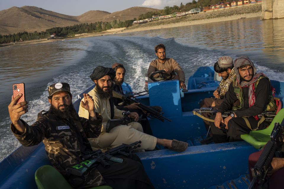 Taliban fighters enjoy a boat ride in the Qargha dam, outskirt of Kabul, Afghanistan, Friday, Sept. 24, 2021. (AP Photo/Bernat Armangue)