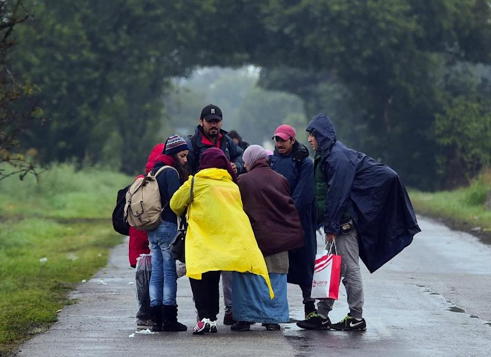 A migrant family hesitates to leave a collection point near Roszke at the Hungarian-Serbian border on September 11, 2015 (AFP Photo/Attila Kisbenedek)