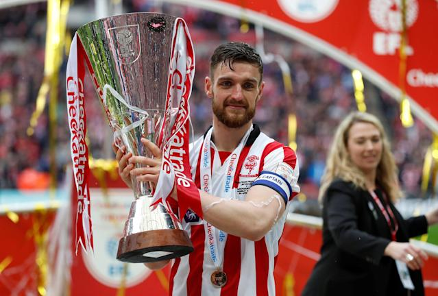 """Soccer Football - Checkatrade Trophy Final - Lincoln City vs Shrewsbury Town - Wembley Stadium, London, Britain - April 8, 2018 Lincoln CityÕs Luke Waterfall celebrates with the trophy after winning the Checkatrade Trophy Final Action Images/Matthew Childs EDITORIAL USE ONLY. No use with unauthorized audio, video, data, fixture lists, club/league logos or """"live"""" services. Online in-match use limited to 75 images, no video emulation. No use in betting, games or single club/league/player publications. Please contact your account representative for further details."""