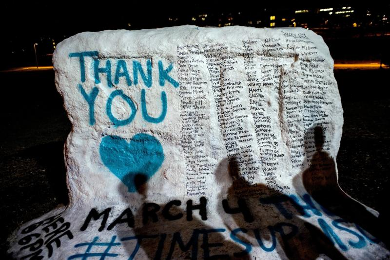"""FILE - In this Jan. 26, 2018, file photo, the shadows of Michigan State University students appear on """"the rock"""" in the university campus which was painted """"Thank You"""" and includes the names of the women who gave victim impact statements during the Larry Nassar sexual assault sentencing hearing in East Lansing, Mich. Michigan State University announced Wednesday, May 16, 2018, that it has reached a $500 million settlement with hundreds of women and girls who say they were sexually assaulted by sports Nassar in the worst sex-abuse case in sports history. (Jake May/The Flint Journal-MLive.com via AP, File)"""