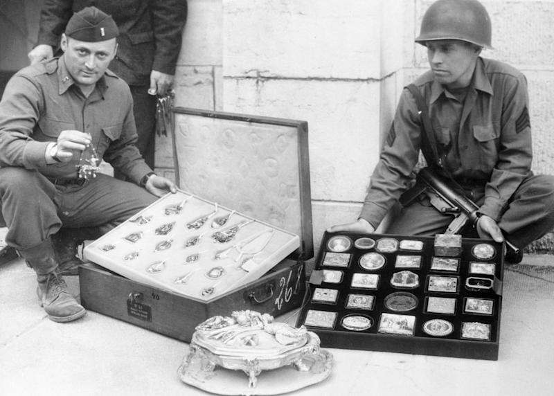 (Original Caption) Yanks of the 7th Army unearth looted art treasures hidden by the Nazis. Here is a tray of valuable antique jewelry and a tray of ornaments, snuff boxes, etc. Holding up a piece of jewelry is Lt. James J. Rorimer of New York City. Holding the tray of snuff boxes is Sgt. Antonio Valin of Salida, California.